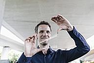 Smiling businessman using portable glass device - KNSF02474