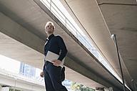 Businessman standing at underpass holding laptop - KNSF02477
