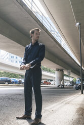 Businessman standing at underpass holding laptop - KNSF02480