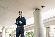 Businessman standing at underpass holding tablet - KNSF02483