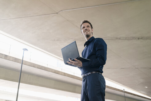 Confident businessman standing at underpass using laptop - KNSF02486