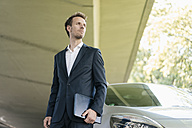 Businessman standing next to car holding laptop - KNSF02507