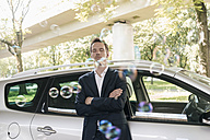 Businessman standing next to car surrounded by soap bubbles - KNSF02510