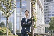 Businessman leaning against a tree in front of office building - KNSF02516