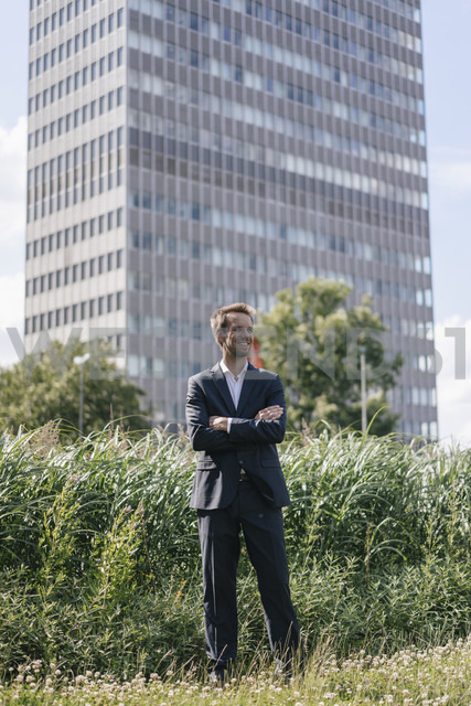 Smiling businessman standing on field in front of office building - KNSF02519 - Kniel Synnatzschke/Westend61