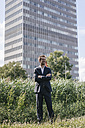 Smiling businessman standing on field in front of office building - KNSF02519