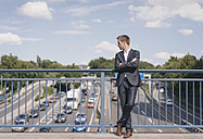 Businessman standing on a bridge over a motorway - KNSF02522
