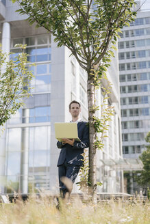 Businessman leaning against a tree in front of office building using laptop - KNSF02525