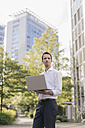 Businessman using laptop in front of office building - KNSF02531
