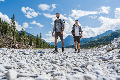 Germany, Bavaria, two hikers walking in dry creek bed - DIGF02781
