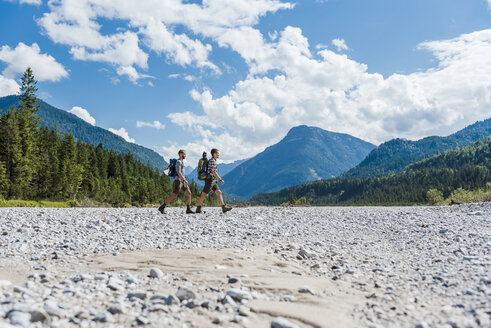 Germany, Bavaria, two hikers walking in dry creek bed - DIGF02784