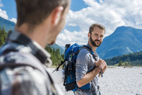 Germany, Bavaria, portrait of young hiker with backpack looking at his friend - DIGF02787