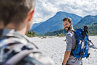 Germany, Bavaria, portrait of young hiker with backpack looking at his friend - DIGF02790