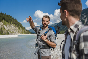 Portrait of hiker pointing on something at distance - DIGF02802