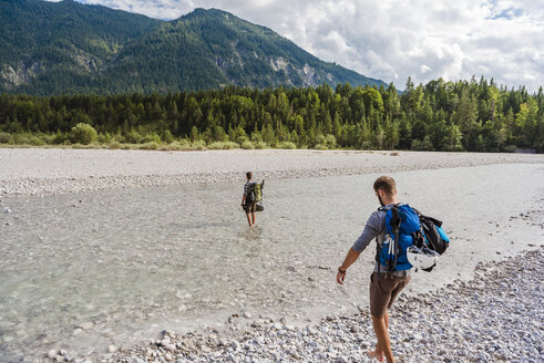 Germany, Bavaria, two hikers with backpacks crossing Isar River - DIGF02805