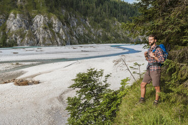 Germany, Bavaria, young hiker with backpack looking at distance - DIGF02814