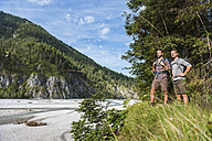 Germany, Bavaria, two young hikers with backpacks looking at view - DIGF02817