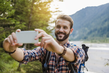 Portrait of smiling young hiker taking selfie with cell phone - DIGF02820