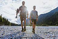 Germany, Bavaria, two hikers walking in dry creek bed at backlight - DIGF02823