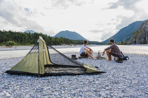 Germany, Bavaria, two hikers camping on gravel bank looking at view - DIGF02829