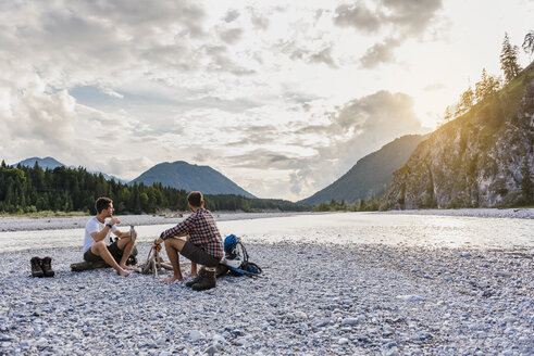 Germany, Bavaria, two hikers having a rest on gravel bank in the evening - DIGF02832
