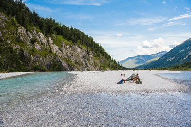 Germany, Bavaria, two hikers camping on gravel bank - DIGF02835