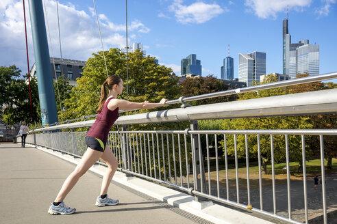 Germany, Frankfurt, young woman stretching on bridge - PUF00692