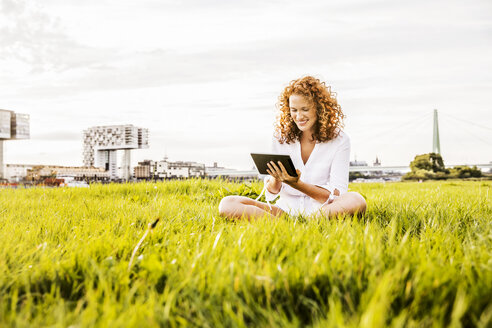 Germany, Cologne, young woman sitting on meadow looking at tablet - FMKF04385