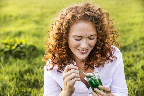 Portrait of smiling young woman eating jelly on meadow - FMKF04388