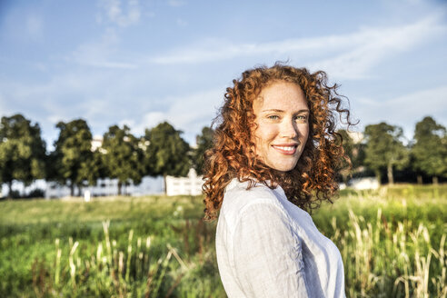 Germany, Cologne, portrait of smiling young woman with curly red hair in nature - FMKF04391