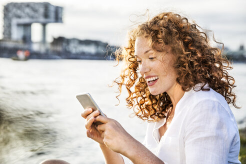 Germany, Cologne, portrait of amazed young woman sitting at riverside looking at cell phone - FMKF04394