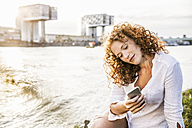 Germany, Cologne, portrait of young woman sitting at riverside looking at cell phone - FMKF04397