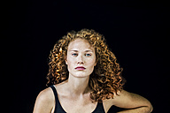 Portrait of freckled young woman with curly red hair in front of black background - FMKF04400