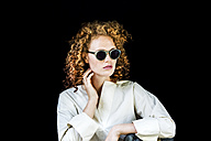 Portrait of stylish young woman with curly red hair wearing sunglasses in front of black background - FMKF04403