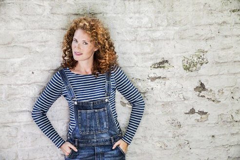 Portrait of smiling young woman wearing denim dungarees leaning against white brick wall - FMKF04412