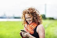 Portrait of happy young woman with curly red hair looking at cell phone - FMKF04418