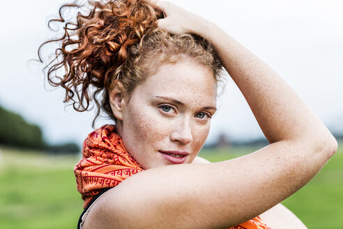 Portrait of freckled young woman with curly red hair - FMKF04421