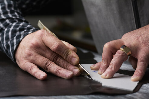 Close-up of shoemaker working on template in his workshop - IGGF00142