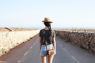 Spain, Menorca, back view of single traveller on county road - IGGF00145