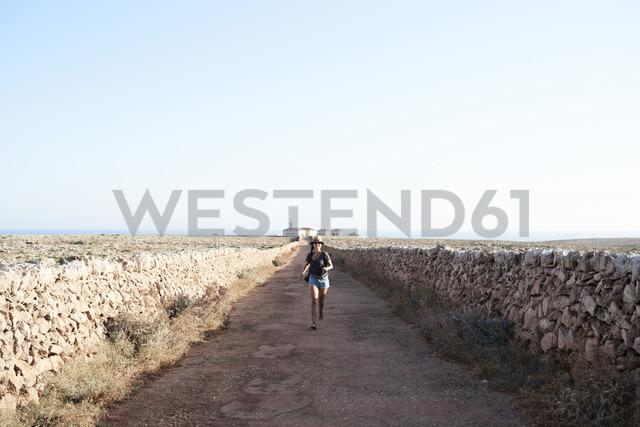 Spain, Menorca, single traveller walking on empty road - IGGF00148