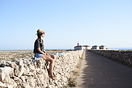 Spain, Menorca, single traveller sitting on natural stone wall looking at view - IGGF00151