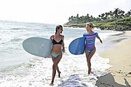 Two women running on the beach with surfboards - ECPF00054