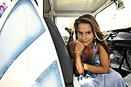 Portrait of woman with surfboard lying in van - ECPF00075