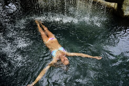 Young woman floating in water in pool with waterfall - ECPF00087