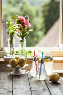 Homemade lemonade with mint on wooden table in front of window - SBDF03297
