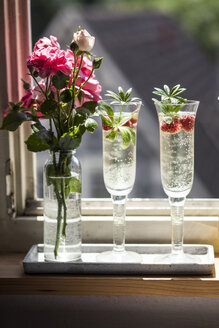 Two Champagne glasses of may wine with raspberries on window sill - SBDF03300