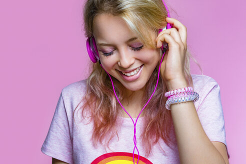 Portrait of young woman listening to music with headphones in front of pink background - MGIF00099