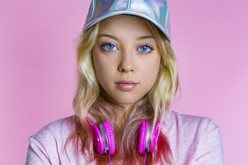 Portrait of young woman with headphones and basecap in front of pink background - MGIF00102