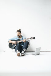 Man sitting with laptop on floor playing guitar - JOSF01525