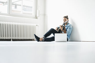 Man sitting with laptop on floor playing guitar - JOSF01528